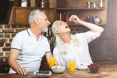 Woman eating cherries. With husband on the kitchen royalty free stock photos
