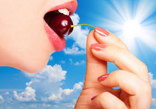 Woman eating cherries. Sky background. Woman eating cherries. Sexy lips take ripe berries in mouth Royalty Free Stock Photos