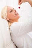 Woman eating cherry on the sofa. A mature woman enjoying cherries on the sofa Stock Photo
