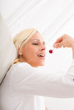 Woman eating cherry on the sofa. A mature woman enjoying cherries on the sofa Royalty Free Stock Photos