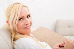 Woman eating cherry on the sofa. A mature woman enjoying cherries on the sofa Royalty Free Stock Images