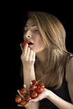 Woman eating cherry tomatoes. Portrait of a young beautiful blonde woman eating cherry tomatoes, isolated against black background Royalty Free Stock Images