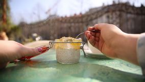 Woman eating chia seeds pudding with mango mousse in jar on the table in cafe. Vegetarian concept. stock video footage