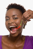 Woman eating chili pepper Stock Photography