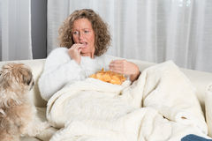 Woman eating chips and looking at dog Royalty Free Stock Photography