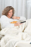 Woman eating chips and zapping Royalty Free Stock Photography