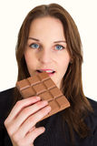 Woman Eating Chocolate. Young Brunette Woman Eating A Milk Chocolate Bar Stock Images