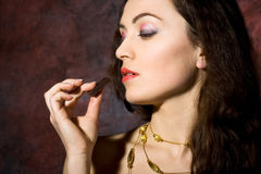 Woman eating chocolate Stock Images