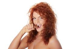 Woman eating chocolate bar. Young beautiful woman eating chocolate bar, isolated on white Royalty Free Stock Image