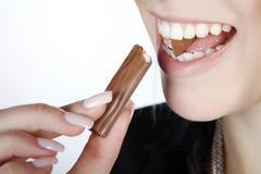 Woman eating a chocolate bar. Beautiful woman eating a chocolate bar Stock Photo