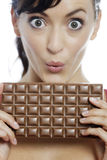 Woman eating chocolate bar. Young woman eating a huge chocolate bar Stock Photos