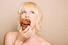 Woman eating chocolate cupcake Stock Photos