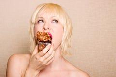 Woman eating chocolate cupcake Stock Photos