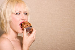 Woman eating chocolate cupcake royalty free stock photography