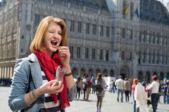 Woman eating chocolate on Grand Place in Brussels. Portrait of a young woman eating chocolate on Grand place in Brussels Stock Photos