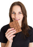 Woman Eating Chocolate and Smiling. Young Brunette Woman Eating A Milk Chocolate Bar and Smiling Stock Photo