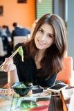 Woman eating Chuka. Young smiling woman eating japanese seaweed salad (Chuka) in a sushi restaurant Royalty Free Stock Photos