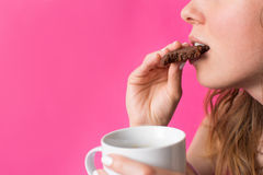 Woman eating cookie with coffee in her hands Stock Photo