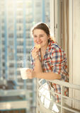 Woman eating cookie and drinking coffee on balcony Stock Photos