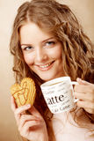 Woman eating cookie and drinking coffee. Stock Photos