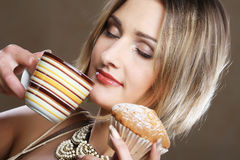 Woman eating cookie and drinking coffee. Royalty Free Stock Images