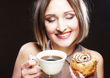Woman eating cookie and drinking coffee. Stock Photo