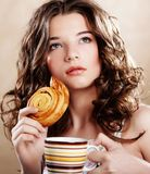 Woman eating cookie and drinking coffee. Stock Image