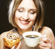 Woman eating cookie and drinking coffee. Royalty Free Stock Photography