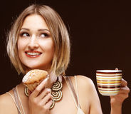 Woman eating cookie and drinking coffee. Stock Photography