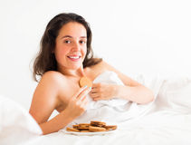 Woman eating cookies in bed Stock Photography