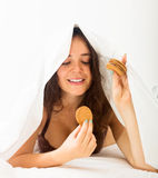 Woman eating cookies in bed Royalty Free Stock Photos
