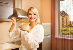 Woman eating cornflakes. Beautiful young woman eating cornflakes with milk in the morning Royalty Free Stock Photography