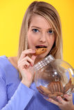 Woman eating crackers Stock Photography
