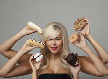 Woman eating cream cakes Stock Images