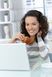 Woman eating croissant Stock Photo