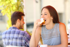 Woman eating a cupcake in a coffee shop Stock Image