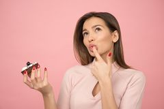 Woman Eating Cupcake While Standing Near Pink Background Inside Room Stock Photography