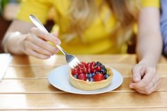 Woman eating custard fruit tart Stock Image