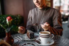 Woman eating delicious chocolate cake in cafe Stock Photo