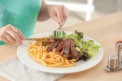Woman eating delicious grilled steak with garnish. In restaurant royalty free stock photos