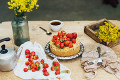 Woman eating a delicious home-made cake with aisheny and stuffed strawberries for dessert. Summer Styled dinner table. Coffee to t Stock Image