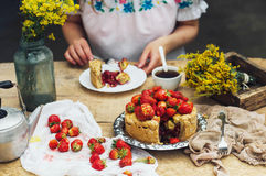 Woman eating a delicious home-made cake with aisheny and stuffed strawberries for dessert. Summer Styled dinner table. Coffee to t Stock Photography