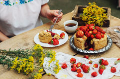 Woman eating a delicious home-made cake with aisheny and stuffed strawberries for dessert. Summer Styled dinner table. Coffee to t Stock Images