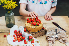 Woman eating a delicious home-made cake with aisheny and stuffed strawberries for dessert. Summer Styled dinner table. Coffee to t Royalty Free Stock Photos