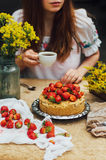 Woman eating a delicious home-made cake with aisheny and stuffed strawberries for dessert. Summer Styled dinner table. Coffee to t Royalty Free Stock Image