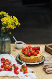 Woman eating a delicious home-made cake with aisheny and stuffed strawberries for dessert. Summer Styled dinner table. Coffee to t Royalty Free Stock Photo