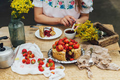 Woman eating a delicious home-made cake with aisheny and stuffed strawberries for dessert. Summer Styled dinner table. Coffee to t Stock Photo