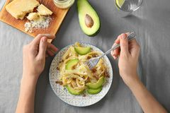 Woman eating delicious pasta with avocado. And cheese at table Royalty Free Stock Photos