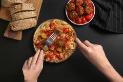 Woman eating delicious pasta with meat balls. And tomato sauce at table Stock Photography
