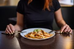 Woman eating delicious quesadilla in restaurant. Young redheaded woman is eating Mexican food in a cafe. Woman eating delicious quesadilla in restaurant. Woman royalty free stock photos